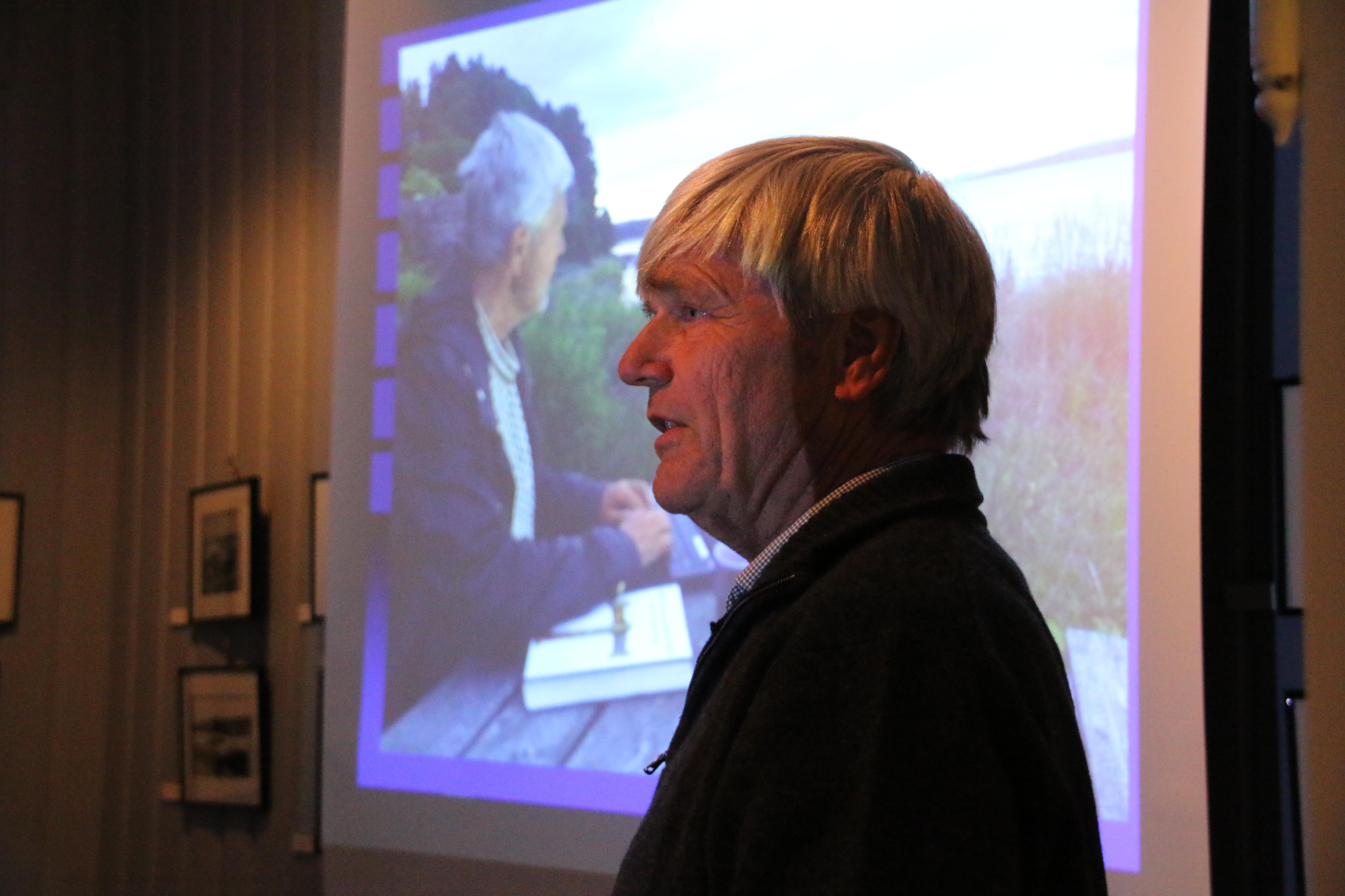 Sverre Jervell foran bildet av seg selv ved bordet nede ved fjorden hvor mye ble notert.